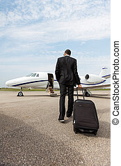 Businessman With Luggage Walking Towards Private Jet