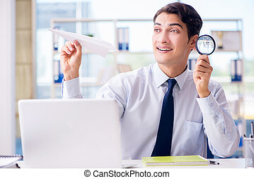 Businessman with magnifying glass and paper plane