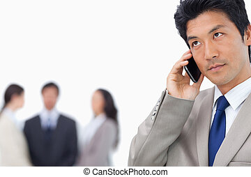 Businessman with mobile phone and team behind him