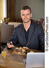 Businessman With Mobilephone And Laptop Having Meal In Restaurant