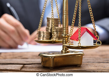 Businessman With Model Home And Coins On Golden Weighing Scale