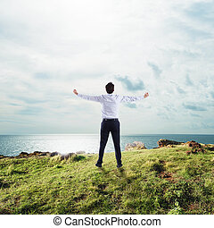 Businessman with open arms to the sky. concept of success and freedom