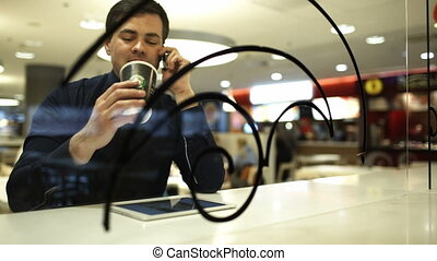 Businessman with pad in cafe talking on the phone