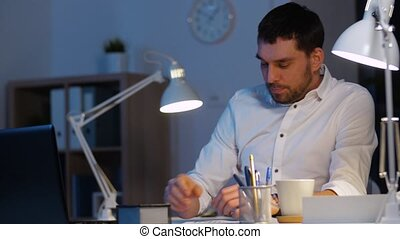 businessman with papers and coffee at night office -...