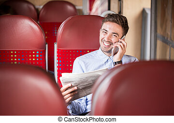 Businessman with phone and newspaper