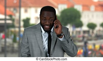 Businessman with phone smiling.