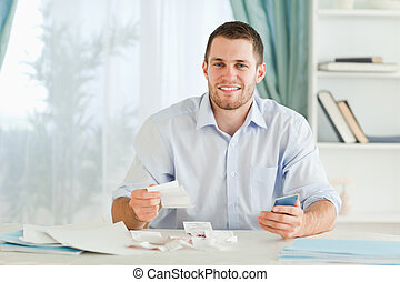 Businessman with pocket calculator checking bills