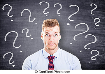 businessman with question marks in front of a blackboard