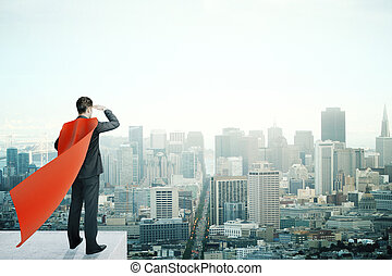 Businessman with red superhero cape standing on pedestal and looking into the distance on cityscape background