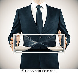 Businessman with sandglass in the hands, frozen time concept