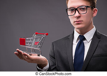 Businessman with shopping cart on gray background