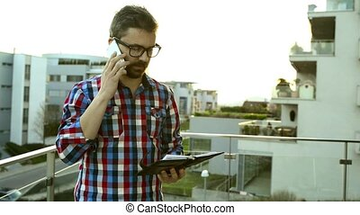 Businessman with smartphone and personal organizer standing on balcony