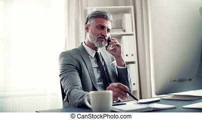 Businessman with smartphone, coffee and computer sitting at...