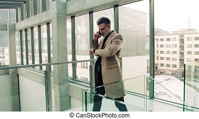 Businessman with smartphone, making a phone call.
