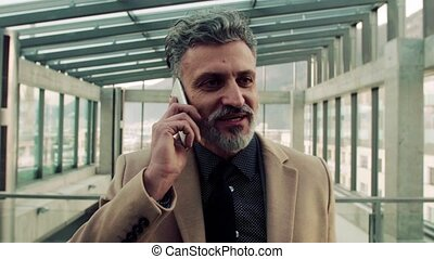 Businessman with smartphone, making a phone call. - Mature...