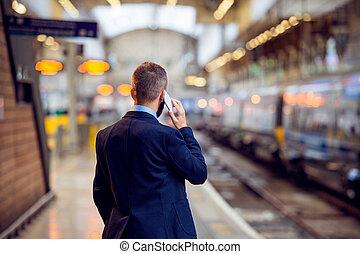 Businessman with smartphone, making a phone call, underground pl