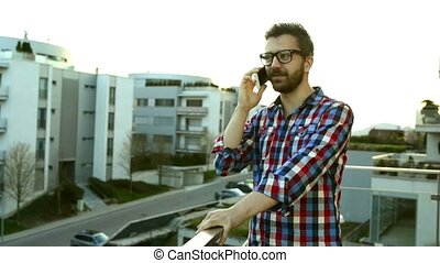 Businessman with smartphone making phone call, standing on balco