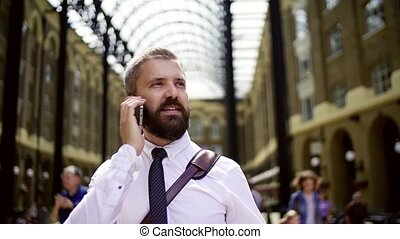 Businessman with smartphone on the trian station in London, making a phone call.