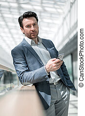 businessman with smartphone standing in the airport building