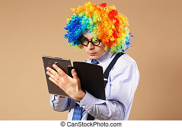 Portrait of business man in clown wig using a tablet to access the internet