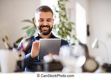 Businessman with tablet in his office.