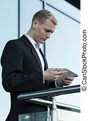 Businessman with tablet outside business centre