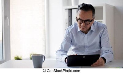 businessman with tablet pc and papers at office