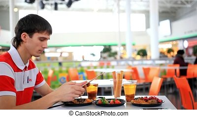 Businessman with tablet pc and some food in cafe. Blurred background. HD. 1920x1080