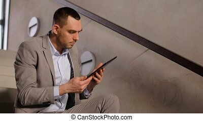 businessman with tablet pc at office stairs