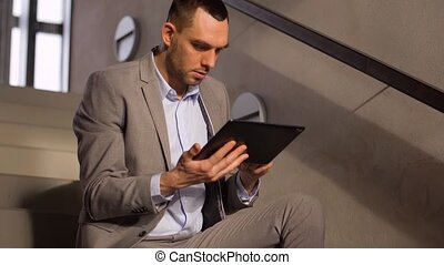 businessman with tablet pc at office stairs - business,...
