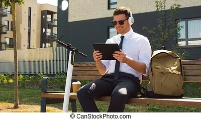 businessman with tablet pc, headphones and scooter -...