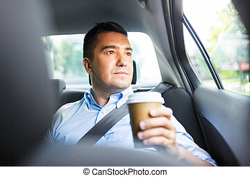 businessman with takeaway coffee on car back seat
