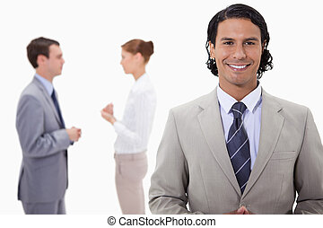 Businessman with talking colleagues behind him