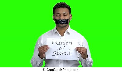 Businessman with taped mouth on Chroma Key background.