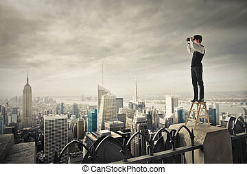 Businessman above city with telescope