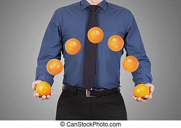 juggling - Businessman with tie juggling oranges, business...