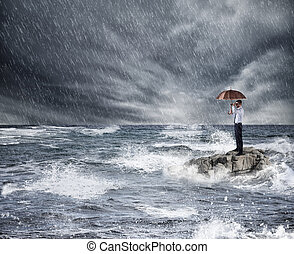 Businessman with umbrella during storm in the sea. Concept of insurance protection