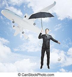 Businessman with umbrella in sky
