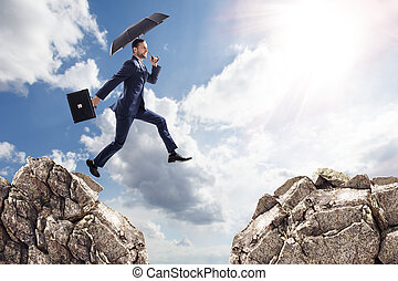 Businessman with umbrella jumping on mountains.