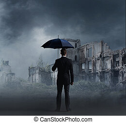 Businessman with umbrella standing over apocalyptic...