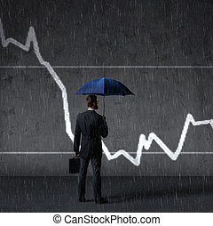 Businessman with umbrella standing over column diagram background. Business, crisis, default concept.