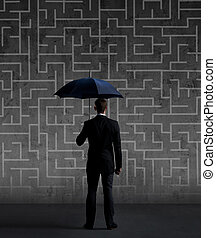 Businessman with umbrella standing over labyrinth background. Business, strategy, insurance, concept.
