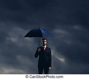 Businessman with umbrella standing over stormy background.