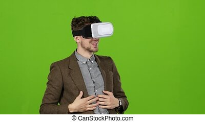 Businessman with virtual glasses looks funny video laughs. Green screen