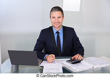 Businessman Working At Desk - Portrait Of A Happy...