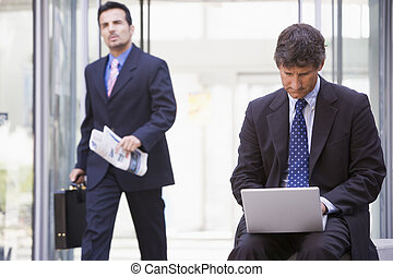 Businessman working at laptop outside