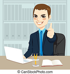 Successful businessman making thumbs up hand sign at his office while working typing on laptop on his desk