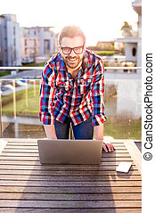 Businessman working from home on laptop, standing on balcony...