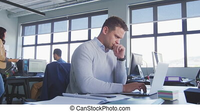 Side view of a Caucasian male business creative working in a casual modern office, using a laptop computer and thinking, with colleagues working in the background in slow motion