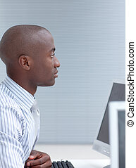 Afro-American businessman working in office with a computer